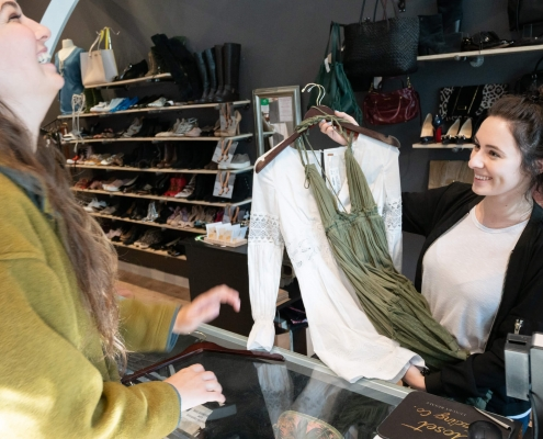 Woman buying white shirt and green dress from a Closet Trading Company Clothing Franchise