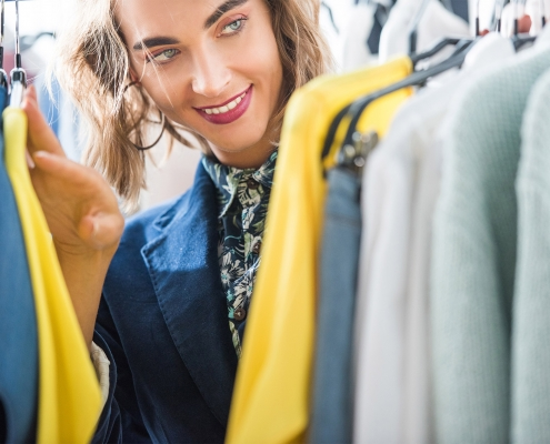 Fashion retailer franchise candidate looking through clothes rack